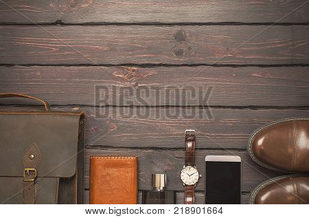 Top view, men's fashion personal belongings and accessories with space on a dark wooden background. Leather bag, shoes, watch.