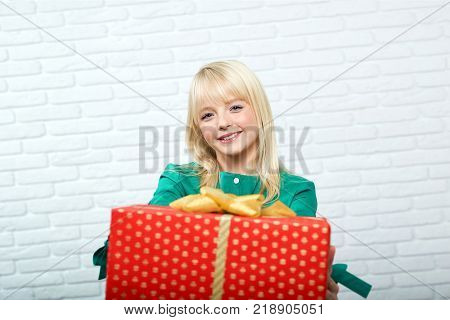 Shot of a young cheerful blonde haired woman smiling holding a present copyspace events mood party celebration happiness Christmas x-mas New Year recreation people.