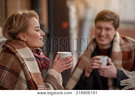 Amorous couple sitting outdoors with cozy blankets. Focus on lady smelling aroma of hot coffee while boy is looking at her with tenderness