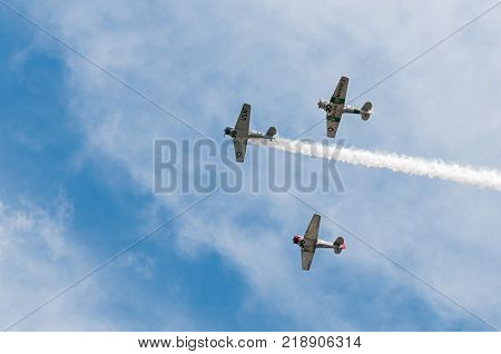 EDEN PRAIRIE MN - JULY 16 2016: Three AT6 Texan airplanes fly overhead with one smoke trail at air show. The AT6 Texan was primarily used as trainer aircraft during and after World War II.