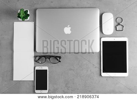 KYIV, UKRAINE - OCTOBER 24, 2017: Apple MacBook Air Silver, iPad mini 4 and iPhone SE Gold on grey background, top view
