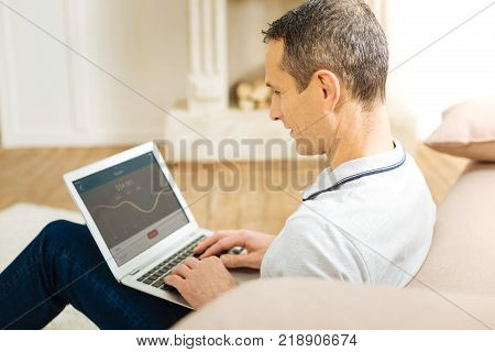 Important statistics. Smart qualified professional worker looking at the screen of his laptop while sitting at home and checking the statistics connected with his main project