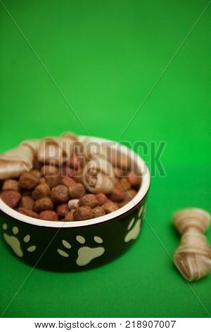 Feed your buddy.A bowl of dry dog food and twisted snacks on a bright one-color green background. Pet care and veterinary concept. Spase for your text or image.