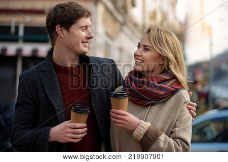 Waist up portrait of amorous man and woman standing together in the street. Male is tenderly hugging female while lady is smiling