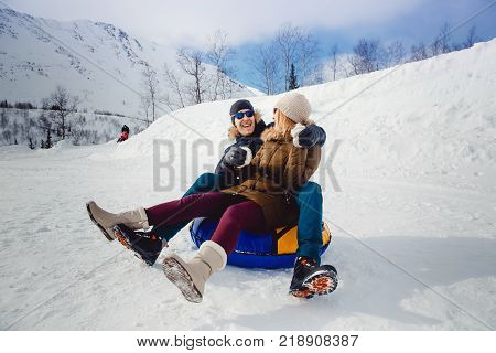 Happy people on tube sledding outdoors in mountains in winter snow. Concept of Christmas holidays