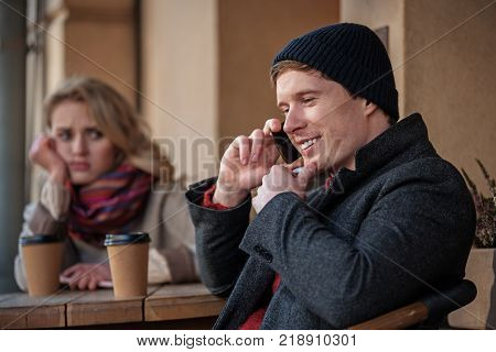 Waist up portrait of young couple sitting at table with hot drinks. Focus on boyfriend talking on phone while girlfriend is bored and showing disappointment