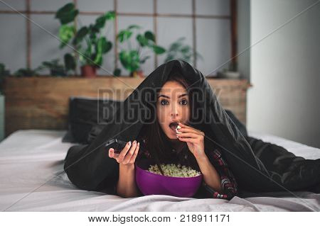 Young woman at home sofa couch in living room watching television scary horror movie or suspense thriller film or horrible news horrified holding remote controller in panic eating popcorn bowl.