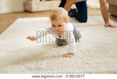 Determination. Pretty little determined child feeling glad while being at home with a kind loving father and crawling on the floor