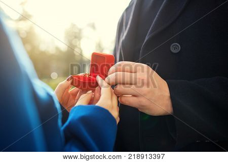 Marriage proposal.  The hands of the pair hold a box with an engagement ring.