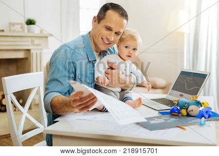 Rather interesting. Positive working man having a productive day while sitting at the table with his cute little calm baby and looking at the important notes connected with his project