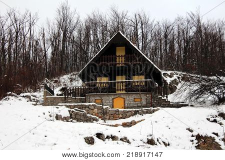 Traditional wooden mountain cottage with stone foundation, picket balcony fence and closed wooden blinds covered in fresh snow and surrounded with trees