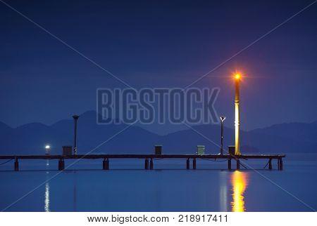 night shot of the marina with pier and lighthouse. Turkey, Gocek.
