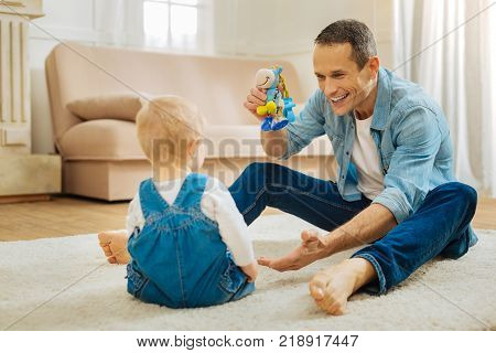 Bright toy. Attentive loving father feeling excited while sitting on the floor with a bright toy in his hand and attracting his childs attention while smiling and showing the new toy