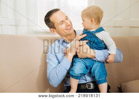 Strong father. Calm concentrated little child looking attentively at the kind loving cheerful father while being in his arms and feeling comfortable