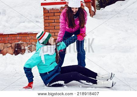 Two happy young girl ice skating in winter Park. It helps other to rise after a fall.