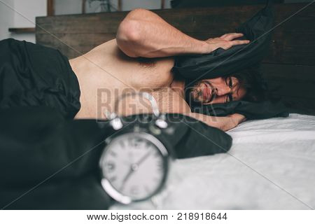 Time to wake up. Tired man in the bed not happy. Mature guy holding alarm clock while checking time for work.