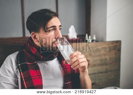 picture from a young man with handkerchief. Sick guy lies in bed and has runny nose. man makes a cure for the common cold Model male has a high temperature, headache, migraine.