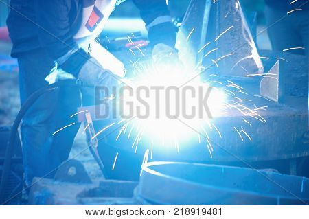 Industrial electrode welder with face shield and blue overall welding a steel pipe in workshop. Close up view.