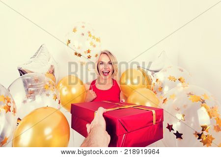 Beautiful blond woman in red t-shirt receives a gift in red packing and gold balloons from man on a white background