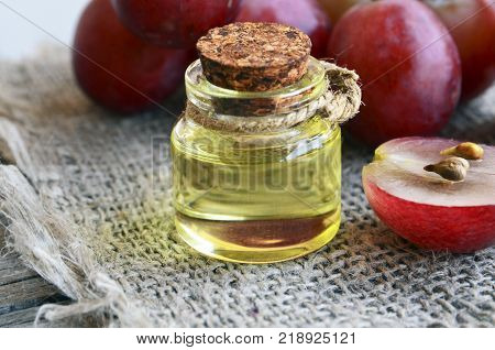 Grape seed oil in a glass jar and fresh grapes on burlap cloth background.Bottle of organic grape seed oil for spa and bodycare and grape berries.Spa,Bio,Eco products concept.Selective focus.