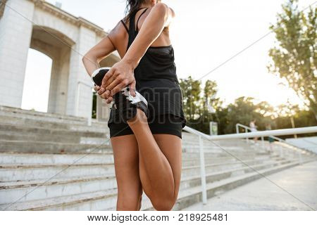 Back view of a fitness woman in earphones stretching her legs on stairs outdoors