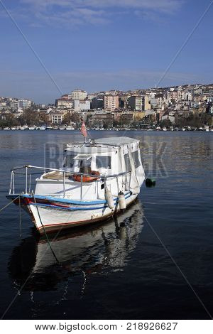 the Anchored fishing boat, stagnant sea goldenhorn