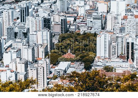 View from high point of modern urban cityscape on very bright summer day: multiple multistorey residential and office buildings park with church in center streets with people; Juiz de Fora Brazil
