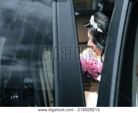 closeup. bride with bouquet sitting in a wedding limo