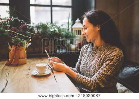 beautiful young girl uses, types text on a mobile phone at a wooden table near the window and drinks coffee in a cafe decorated with Christmas decor. Dressed in a gray knitted wool sweater.