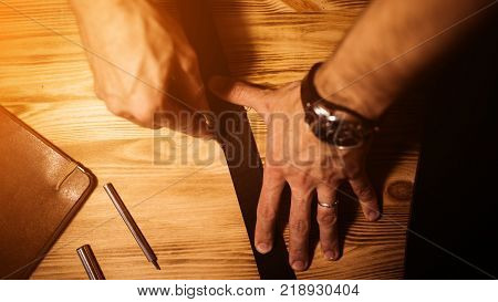 Working process of the leather belt in the leather workshop. Man holding tool. Tanner in old tannery. Wooden table background. Close up man arm. Warm Light for text and design. Web banner size.
