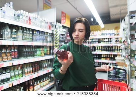 Portrait of a girl looking at a bottle of wine in her hand during shopping. Shopping for alcohol in a supermarket. The choice of wine in the store. Shopping in a supermarket