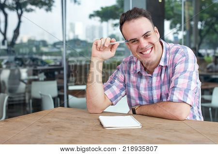 Cheerful handsome businessman working in sidewalk cafe. Optimistic young freelancer having break and thinking of business ideas. Leisure concept with simple guy