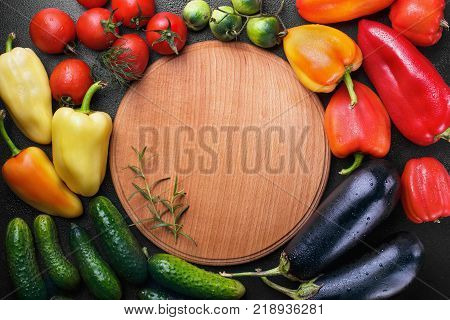 A lot of vegetables Sweet pepper, cucumber, eggplant, tomatoes, green tomatoes on the stone black background.Round desk with rosemary in the midlle free space.Background.A lot of vegetables Sweet pepper, cucumber, eggplant, tomatoes, geen tomatoes on the