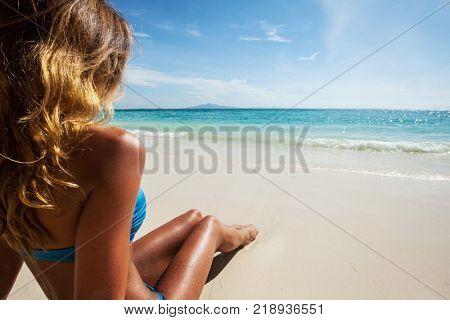 Beach holidays woman in bikini enjoying summer sun sitting in sand looking at sea
