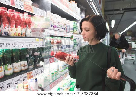 The girl is shopping at the supermarket. A beautiful girl holds yogurt in her hands and looks carefully at his label. Shopping in a supermarket.