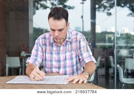 Pensive man searching job in newspaper while sitting in sidewalk cafe. Busy young man in casual clothing reading newspaper in summer and making marks with pen. Unemployment concept
