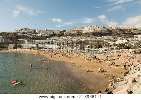 GRAN CANARIA, SPAIN - DECEMBER 10, 2017: People visit Puerto Rico Beach in Gran Canaria, Spain. Canary Islands had 13.3 million visitors in 2016, with Gran Canaria as the second most visited, after Tenerife.