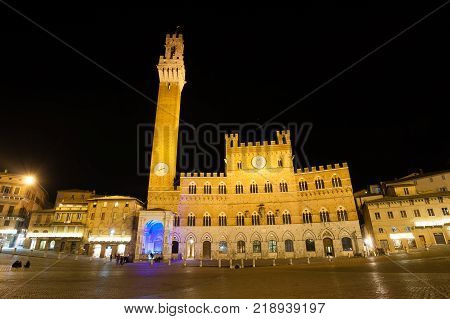 Night view of Campo Square (Piazza del Campo) Siena Palazzo Pubblico and Mangia Tower (Torre del Mangia) in Siena Tuscany Italy.