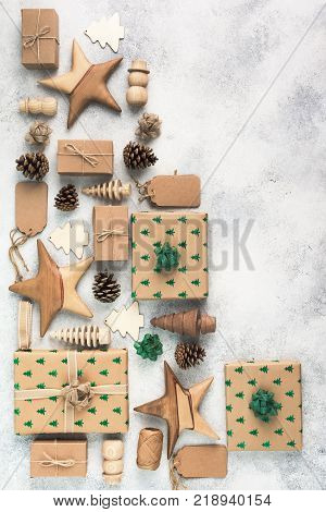 Christmas arrangement, brown present boxes with sparkling embossed fir trees, pine cones, gift tags, wooden decorations, jute twine, top view, copy space for text, vertical