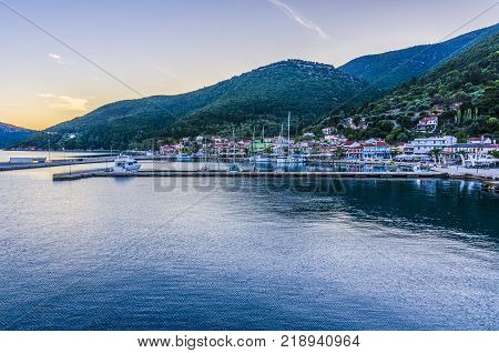 Panoramic view from the sea of the port of Sami with its moorings the port facilities and back the mountains illuminated by the sunset sun Kefalonia