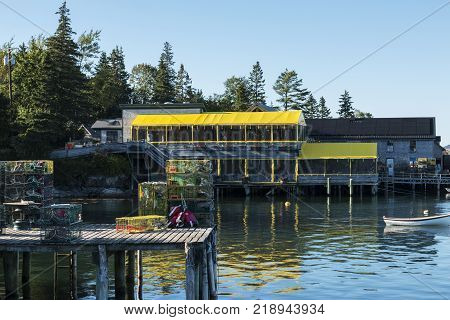 A postcard view of Bass Harbor Maine with a pier of lobster traps Thurstons lobster pound restaurant with yellow roof and a small row boat mored in the harbor