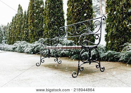 A Park bench covered with snow. Snow, beautiful snow, nice weather. Isolated place for text
