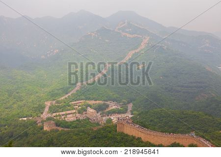 Beijing, China - August 10, 2017: Crowd tourists climb Badaling Great Wall near Beijing. The Ming dynasty walls measure 8, 850 km in length, from China's East coast till the Gobi desert in the West.