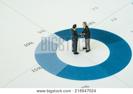 Agreement or deal for business success with miniature businessmen handshaking on printed performance pie chart or graph.