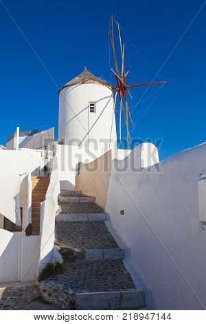 The traditional windmill up the cliff at Oia Town, Santorini, Greek Island. Traditional windmill is one of the symbol of Oia Town, the most famous town in Santorini.