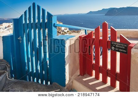 Two colorful wooden fence gates with lable No entry in Oia on Santorini island, view on caldera with vulcano island Nea Cameni. Greece. Cyclades islands, Agean Sea, Greece, EU