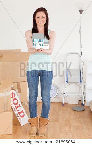 Attraktive Rothaarige Frau hält eine Miniatur Haus stehen auf dem Boden zu Hause