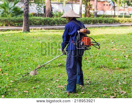 The worker of a garden cuts off a grass. The man in a uniform of the general worker works at a lawn. Work of municipal services on improvement of territories.