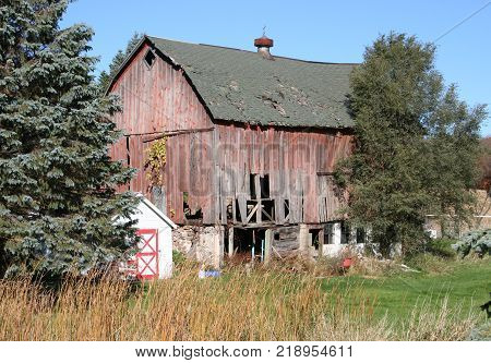 A dilapidated red barn with a sagging roof and multiple holes.