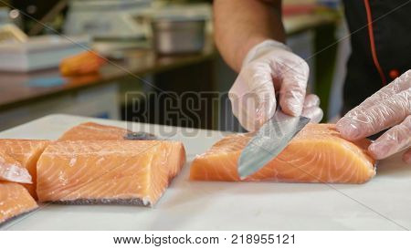 Close-up of sushi chef in gloves slices fresh salmon at sushi bar. Professional cook cutting fish fillet at commercial kitchen.